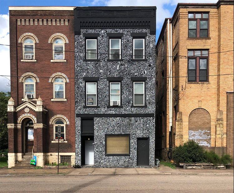 A photo of three brick buildings along Braddock Avenue. The center building stands out with an intricately detailed black and white mural painted across its façade.