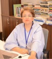 A photograph of Nausheen Anwar seated at a desk