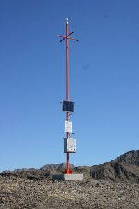 A large, orange rescue beacon that looks like a telephone pole stands in the middle of a remote desert.