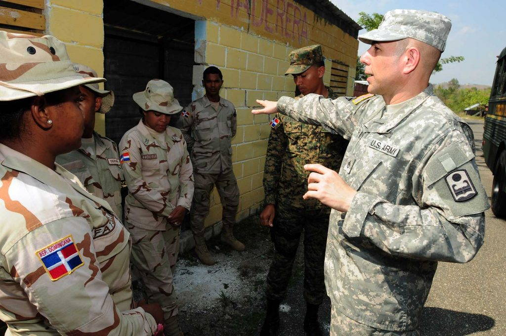 U.S. military officer points toward Dominican border control officers