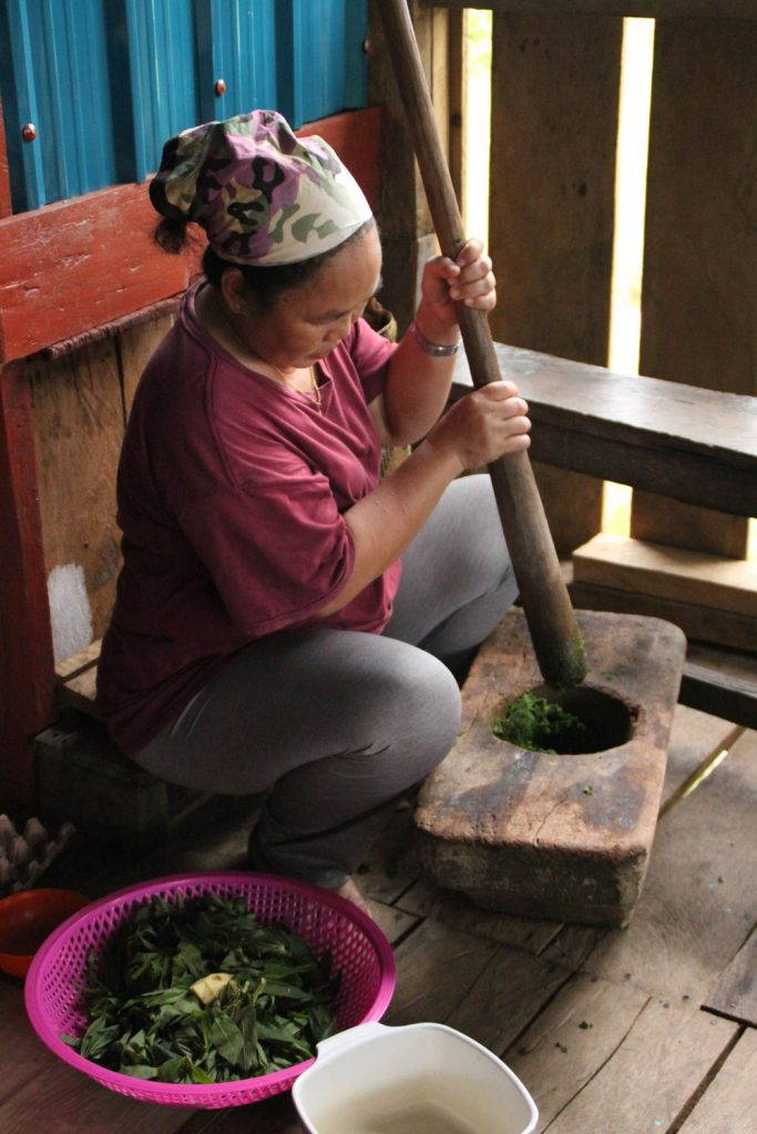 Woman pounding tapioca leaves in a wooden mortar