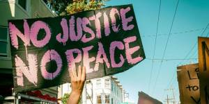 Image a protest. A hand holds up a sign that reads No Justice No Peace