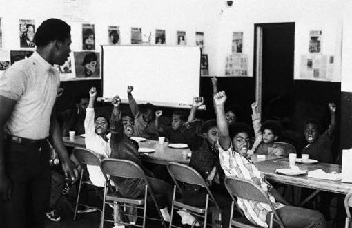 Black and white photo of children sitting at a table, posing for the camera with raised fists.