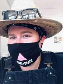 """Headshot of a person wearing overalls, a straw hat with black sunglasses resting on the brim, and a black mask with a pink triangle and the phrase """"Silence=Death"""" in white text."""