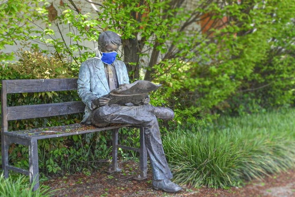 Statue of a man sitting on a bench wearing a mask and reading a newspaper