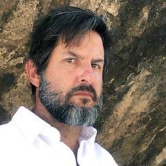 Headshot of a man with dark hair and graying beard.