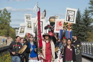 Ojibwe protestors march against the Line 3 pipeline, carrying signs and chanting