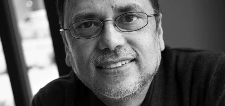 Black and white photograph of a man wearing glasses. Headshot of Dipesh Chakrabarty