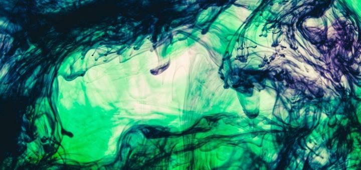 Green and purple ink swirls in water