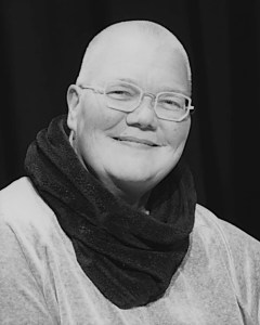 Black and white photograph of a smiling woman with a bald head wearing glasses and a scarf.
