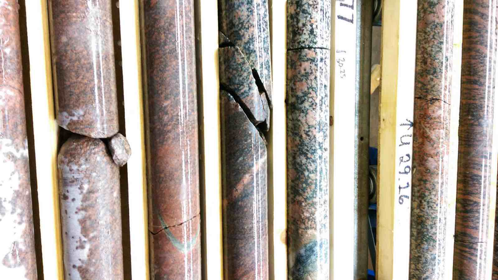 Cylinders of polished stone in various colors separated by planks of wood