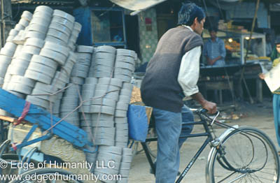 India - Man transporting a large load of goods using a bicycle.