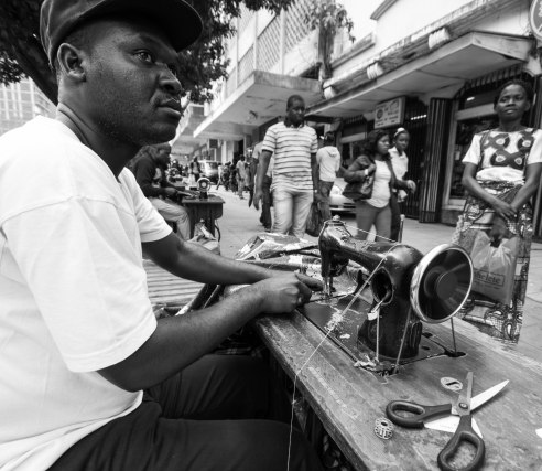 A tailor sews on the dilapidated footpaths of Maputo, Mozambique