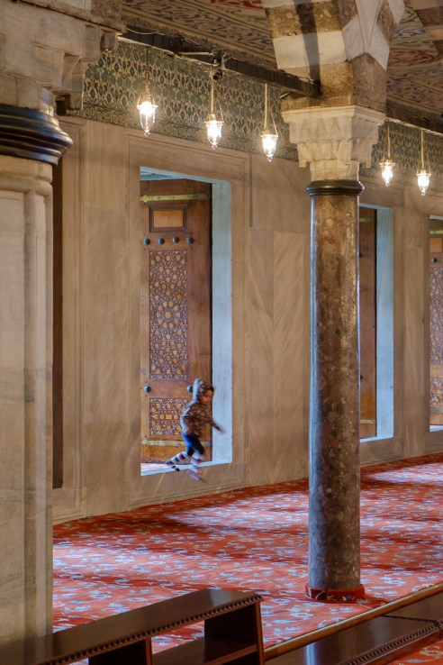 Sultanahmet Camii - a young girl enjoys the spacious freedom of the prayer hall.