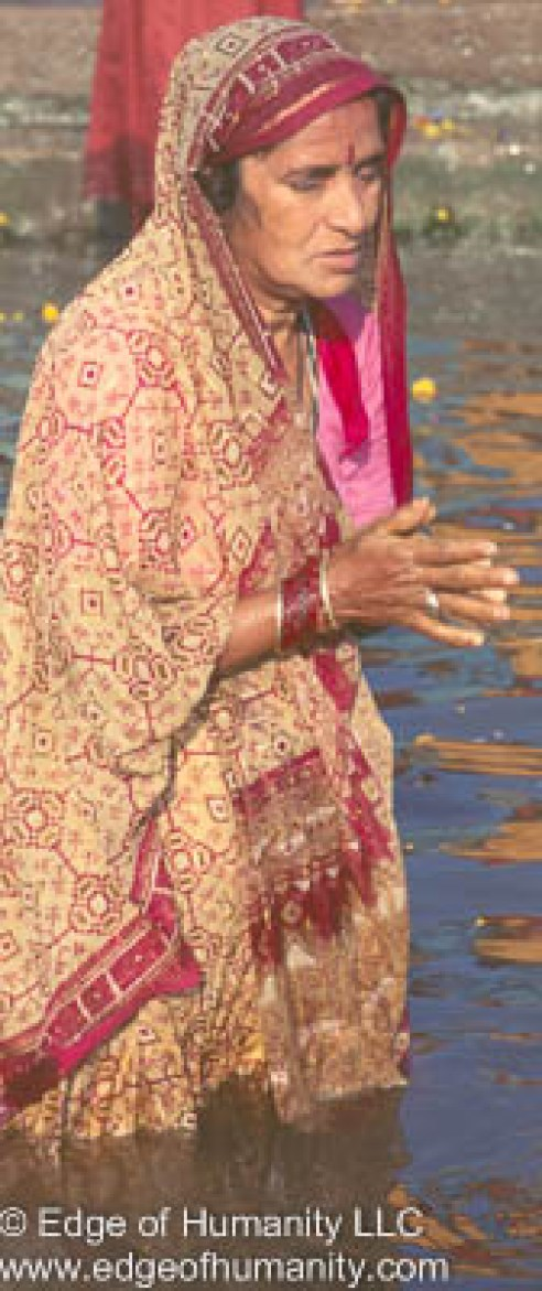 Woman praying in the Ganges River, Varanasi, India.