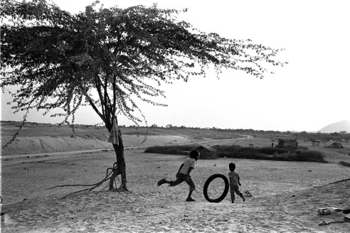 Children are playing with the old motorcycle tire in the desert village Rural Rajasthan, India