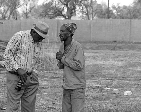"""""""Lend me your ear""""<br /> This is still one of my favorite street photographs from when I was just starting out. Shot at a 'shebeen' ( illegal tavern selling alcohol). A place where locals can get together especially on a Sunday, enjoying one or two cold ones. The two in this image are from very different walks of life. They weren't necessarily socializing, but the gentleman on the right had something urgent and wanted to be heard."""