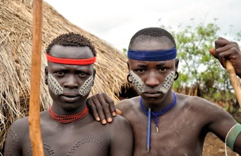 Mursi boys in a village. Omo river valley, Ethiopia.