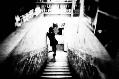 I sort of want you to stay: A girl takes a call on the stairs of a Seoul restaurant. South Korea