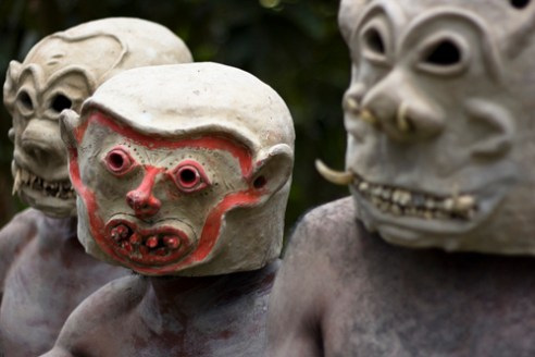 The warriors arrive stealthily creeping into the village, skin grey from dried mud, arms adorned with leaves and flowers; and incredibly heavy clay masks with grotesque faces covering their heads. Asaro Mudmen Tribe - Goroka, Central HIghlands, PNG
