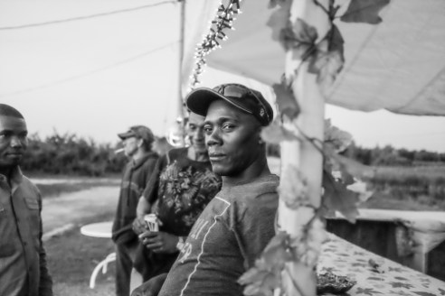 Enjoying the music as his fellow farm workers prepare for an evening of food and festivity at their harvest party in Upstate NY