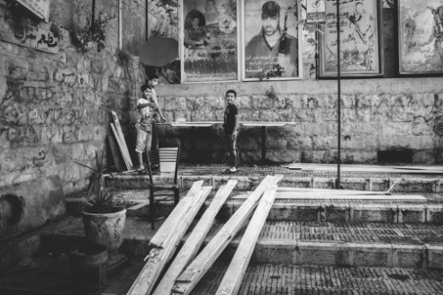 Palestinian Boys Nablus June 11, 2015 - Palestinian boys clean planks of wood in front of images of Palestinian martyrs in Nablus.