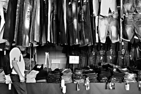 Man looking for trousers in Els Encants market. Barcelona, Spain