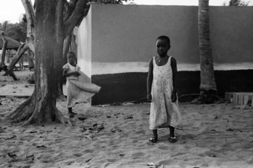 The wind is rising The wind plays with the dress of the young girl in the background, while ignoring the other. It is January, when is blowing the Harmattan, this wind loaded of sand coming from the desert. The sky is becoming milky, and the light diffuse. In 2005, after Eyadéma death, a wind of hope raised as elections were coming, after 38 years of dictatorship. A wind of wrath, from men and women who went in the streets to claim for a real democracy. Opponents murders, massive repression of protests, electoral fraud,.... Human Rights League, European Union, United Nations denounced the legitimacy of the new power. French president Jacques Chirac congratulated the new president. The