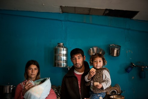A couple with their newborn baby and their niece. the hole in the ceiling leaks water into the kitchen.