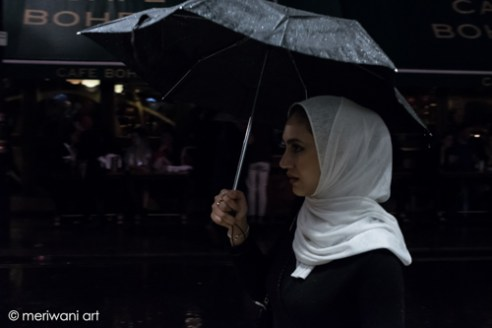 Central London, A young lady is shelter under her black umbrella in a rainy night