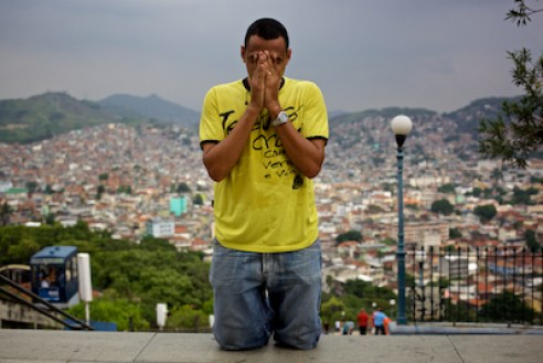 March 2011. A man prays outside Nossa Senhora Da Penha Church in Rio de Janeiro. The Vila Cruzeiro community is in the background. This man had crawled up the more than 300 steps to the church on his hands and knees - an act of giving thanks for granted prayers.