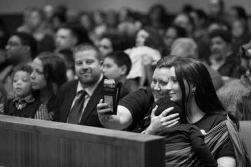 "Danielle Sharkey (left) and Ali Beck (right) take a ""selfie"" with their daughter Kendrik Sharkey during the Adoption Day ceremony at the Monroe County Courthouse in Rochester, N.Y. on Nov. 20, 2015. Over a dozen families all adopted children at the courthouse for Monroe County's annual Adoption Day. There are over 450 children currently in foster care in Monroe County, out of over 400,000 in the nation."