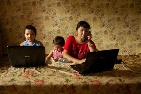 Maxim and his family surrounded by their technology.