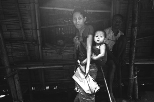 A Nocte Tribe woman with her child in the village of Noksa, Tirap District. The tribe is believed to belong to the Indo-Mongoloids racially, with distinct and varied culture, language dress and customs. If Naga legend is to be followed, they came down from Burma (Myanmar) through the Patkai Range. The Migration is presumed to have taken place between 7-8 century B.C. or earlier.