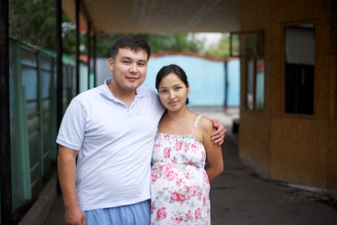 Arman and his wife Janna stand outside their home. They are newly married and expecting their first child.