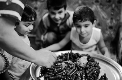 Ritual waitChildren are waiting for the end of their grandmother prepare delicacies popular dishes which is called (Grapes Leaves-Dolma) 2010-02-03