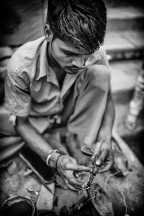 Shahpura Village, Rajasthan, India. A street leather worker gives my camera strap some much needed attention. He glues then stitches a toggle back onto the strap.