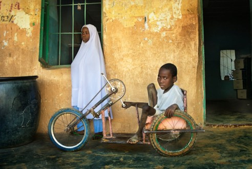Polio victims Naja Atu Yusif (L) and Adamu Yusif (R), in the courtyard of their primary school in Kano. While Naja can limp, Adamu can't walk and has to use a tricycle to move around. Kano, Nigeria