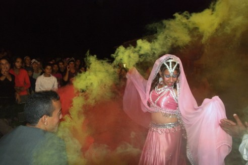 Midnight dancing in front of the community A bride dancing under the colored fog before henna ceremony, members of the community are watching in the darkness behind. Photo was taken in 2007 in Thrace, in a Gypsy neighborhood.