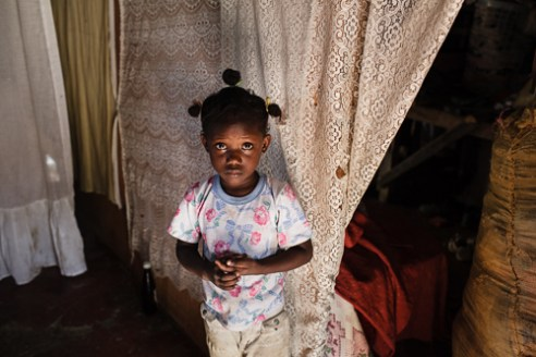 Oshkosh Young girl inside her home. Although a tin hut people try their best to decorate.