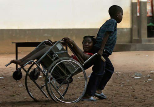 A young boy helps his sister (no names) by pulling her and wheelchair across a Primary school playground in Mausse. The school has a localy-intergrated network in HIV/AIDS activities. The group includes 35 pupils and 5 teachers