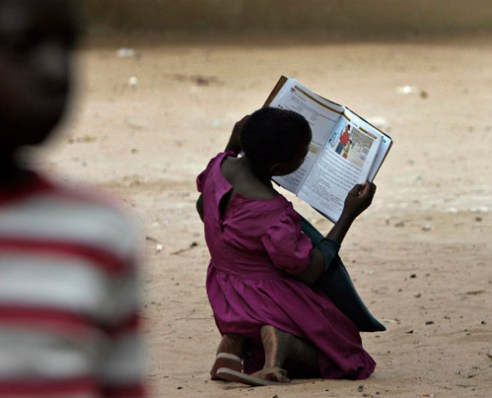 A young girl reads a book on HIV Aids outside her Primary School after classes were dismissed for the day in Mausse, Mozambique. (2005)