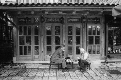 Chess players shelter from a rain storm in Sarajevos's old town, Bascarcija.