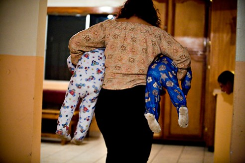 """Tía"" Ana Rosales carries Hector Galvez, 2, and J. J. Hernandez, 19 months, to bed. The number of children can fluctuate, depending on the time of year."