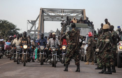 People drive into Uganda from South Sudan. The Uganda military controls the influx of refugees.