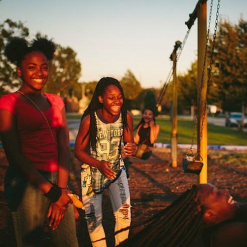 """East Chicago, Indiana From left, friends since childhood, Janae Peyton, 13, Ashanti France, 12, Irene Wooley, 13, and Tniyah Foxx, 12, swing at the park near the West Calumet Housing Complex in East Chicago, Indiana. The playground is part of the Carrie Gosch Elementary School, which has been turned into an EPA office. """"All my memories are here. I've got to move away from my friends,"""" Peyton said. 