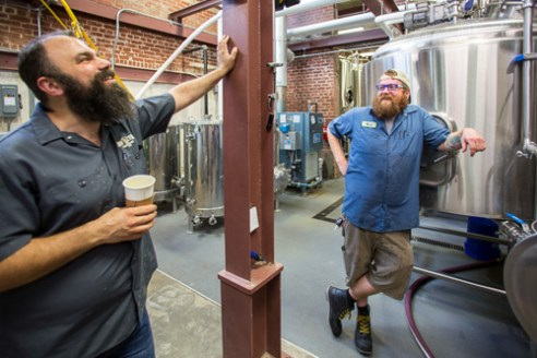Saxapahaw, North Carolina - Wednesday July 13, 2016 - Ben Woodward, founder of Haw River Farmhouse Ales, talks with brewer Nick Williams while at the brewery in Saxapahaw, North Carolina.