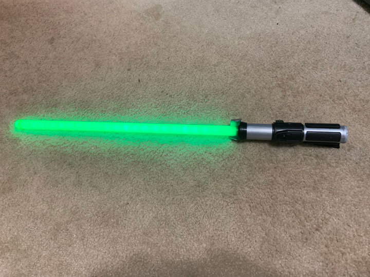 Green lightsaber toy with blade turned on