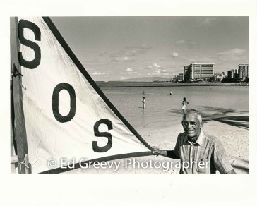 Save Our Surf founder John Kelly holds SOS banner at thr Kapahulu Groin on %22Clean Water Day%22 rally. 8028-2-4 8-19-95