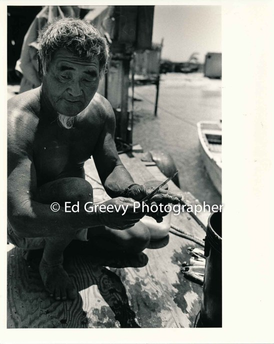 Mokauea Island fisherman cleaning his catch. 2914-7-2A 8-26-75